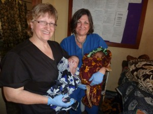 Nancy Comello and Karen Klemp with two of the babies they helped deliver in January 2014.